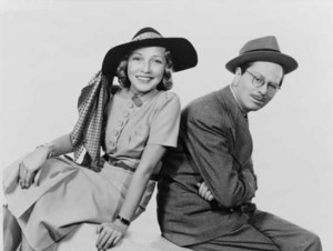 Publicity portrait of the fashionably hatted Jane and bespectacled Goodman